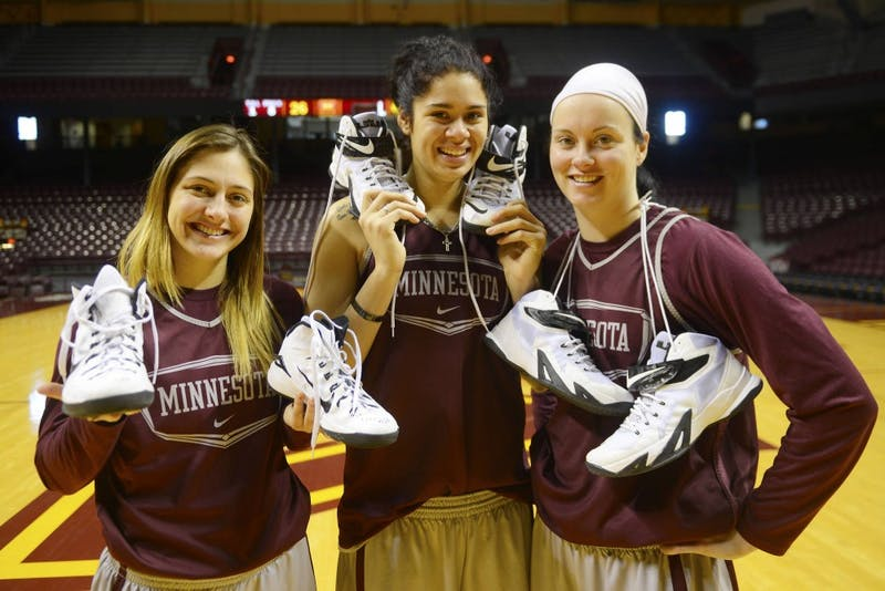 Gopher women's masketball players Shayne Mullaney, Amanda Zahui B. and Kayla Hirt pose with their athletic sneakers in the Williams Arena on Friday afternoon.