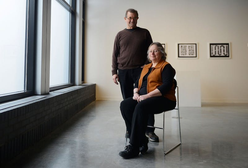 "James Henkel, left, and Joyce Lyon pose together inside their exhibit entitled ""The Longest Way Round is the Shortest Way Home"" at the Nash Gallery in the Regis Center for Arts on Friday afternoon. The exhibit celebrating the work and careers of the two University professors premieres today, and is open from 11:00AM to 7:00PM."