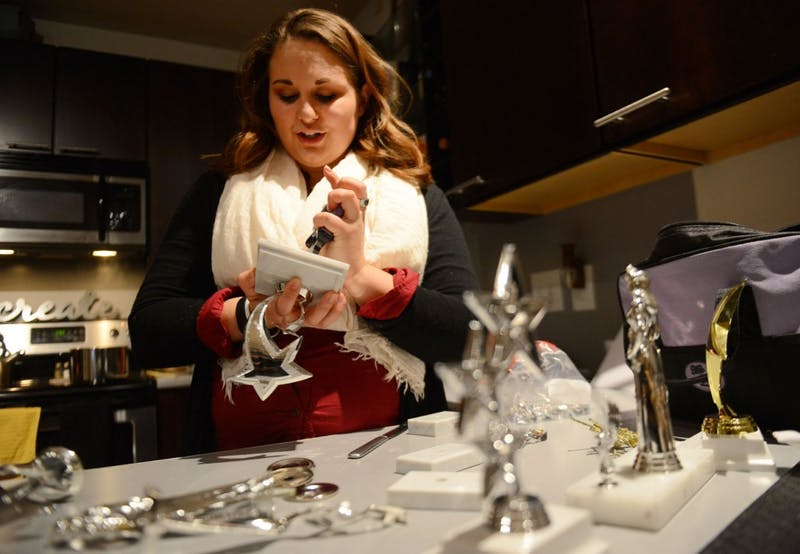 Senior and co-director of the Minnesota Miss Amazing Pageant Jordan Crosser assembles trophies in her apartment in Uptown on Monday evening in preparation Saturday's event.