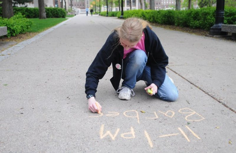 Mathematics senior Melissa Checky chalks announcements about IT Week on Sunday in the Northrop Mall area.