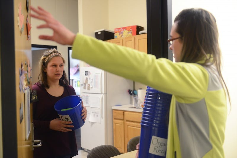 Environmental science and management sophomore Claudia Althoen explains the Minnesota Student Association's organics initiative to student Paige Adams in Yudof Hall on Friday, March 10, 2017.