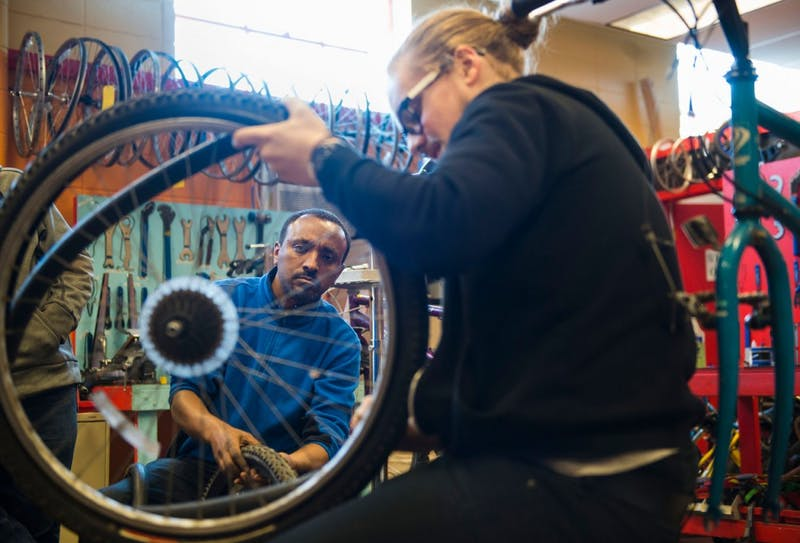 Earn-a-Bike student Wondey Geta observes as mechanic Ben Swanson demonstrates how to remove a bike tube at SPOKES on Saturday morning.