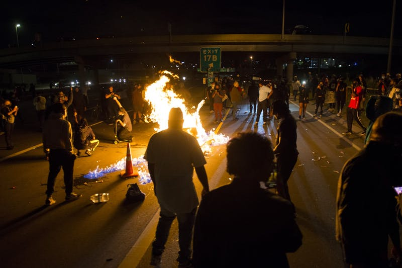 Protestors attempt to block traffic and light a fire on Interstate 35W on Friday, May 29.