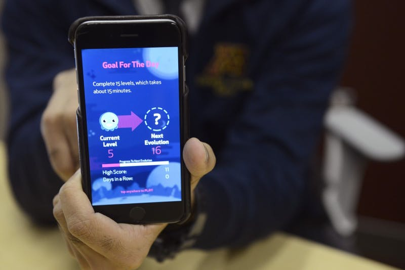 Dr. Umesh Goswami holds a cell phone displaying Soundly on Wednesday, Oct. 4. The app uses a game format to exercise the vocal muscles that cause snoring, and has reduced snoring in some patients by 20 percent.