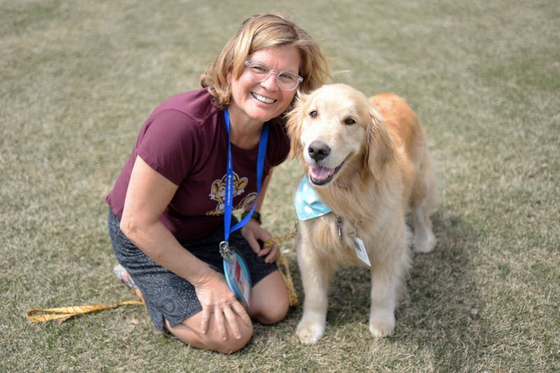 Holly Parker and Bailey the golden retriever pose for a portrait outside of the Masonic Children's Hospital after volunteering in a hospital unit on Tuesday, May 1.