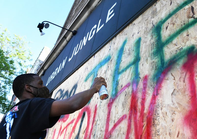 "Tommie Daye, owner of Urban Jungle, spray paints ""Stop the Violence"" on his boarded-up shop window in the Cedar-Riverside neighborhood on Thursday, May 28."