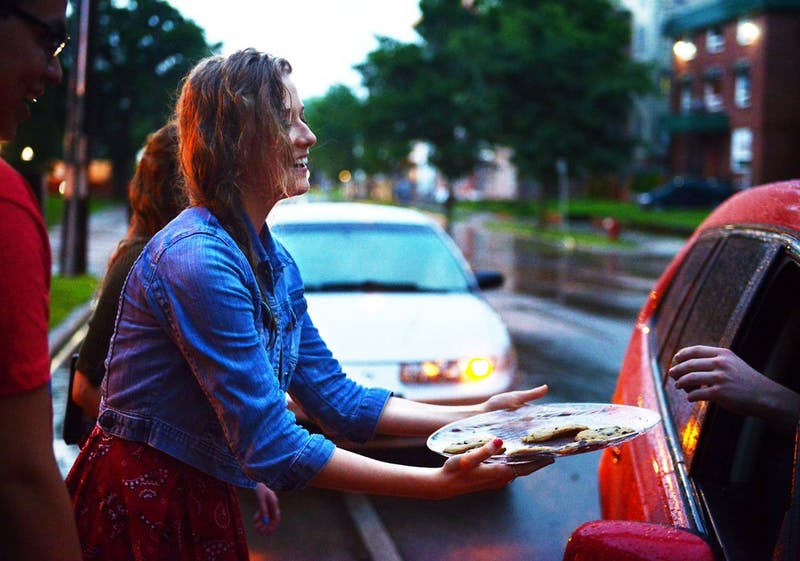 The Church of Jesus Christ of Latter-day Saints member Victoria Paider hands out cookies to stalled cars after the rainstorm caused flash floods along University Avenue on Friday, June 21, 2013 outside the Minneapolis LDS Institute of Religion.