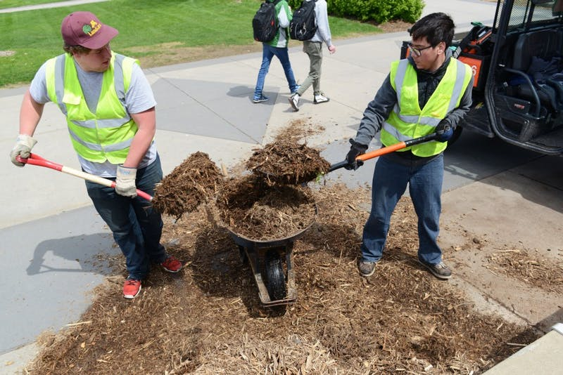 Asian Languages and Literatures and Physiology freshman Jacob Miller, left, and Microbiology and Biochemistry sophomore Tanoa Thome spread mulch outside Coffman Memorial Union on May 2, 2017.