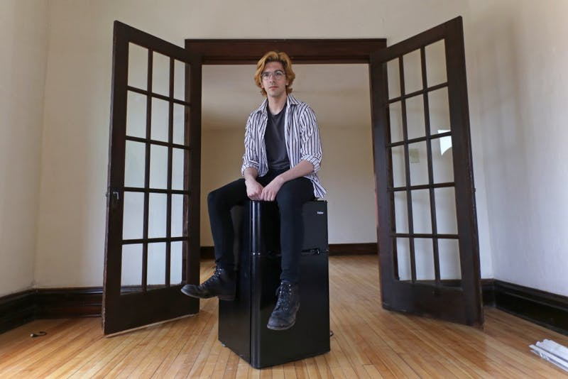 Computer science major Jeremiah Michalik poses for a portrait in his empty apartment on Tuesday, April 24 in Minneapolis. Michalik struggles to pay his $500 monthly rent, so he's adding a commute to school and moving to Crystal, Minnesota to cut costs.