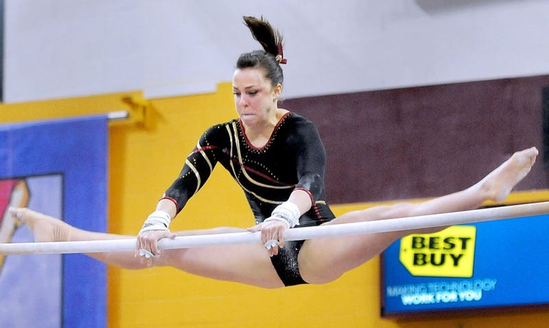 Senior Kayla Slechta competes on bars, March 9, 2013 in a quad meet at the Sports Pavilion.