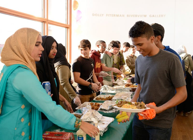 "Freshman Moaaz Elmubark (right) gets food at the Al-Madinah Cultural Center hosted ""Eidrageous"" dinner at the Weisman Art Museum on Thursday evening."