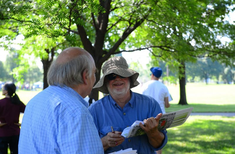 St. Anthony Falls Heritage Board member Ted Tucker reviews two draft designs for Logan Park in Minneapolis on Saturday, July 14 during the twentieth annual East of the River bus tour of neighborhood parks in northeast and southeast Minneapolis.