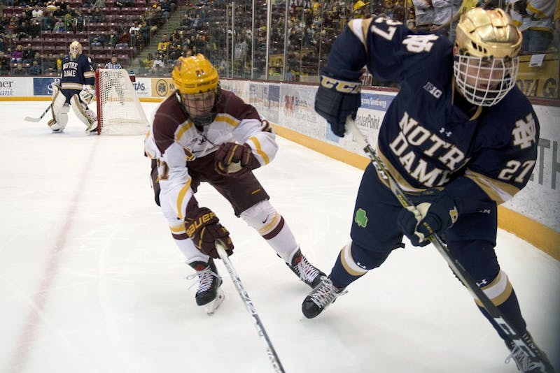Freshman forward Casey Mittelstadt reaches to take the puck from Notre Dame defenseman Bobby Nardella on Friday, Jan. 26, 2018.