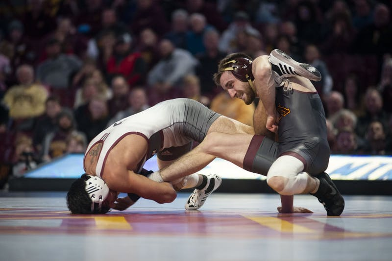 Redshirt Senior Carson Brolsma holds an opposing Rider wrestler at Williams Arena on Friday, Nov. 15. The Gophers went on to fall to Rider with a final score of 21-17.