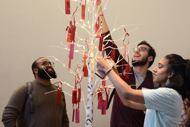Event goers place their pieces of paper on a tree at Weisman Art Museum Friday, Nov. 3.