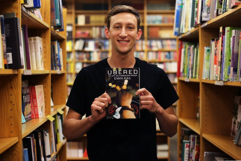 "Evan Kail, author of ""Ubered"" poses with a copy of his book at Magers & Quinn bookstore on Tuesday, May 29, 2018 in Minneapolis. Kail no longer drives Uber."