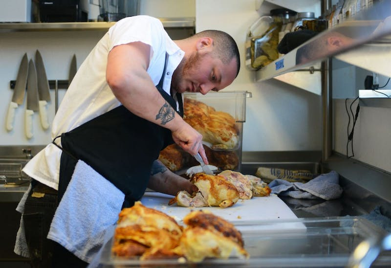 Prep Chef Aaron Colgrove prepares chicken at Coup D'Etat on Tuesday.