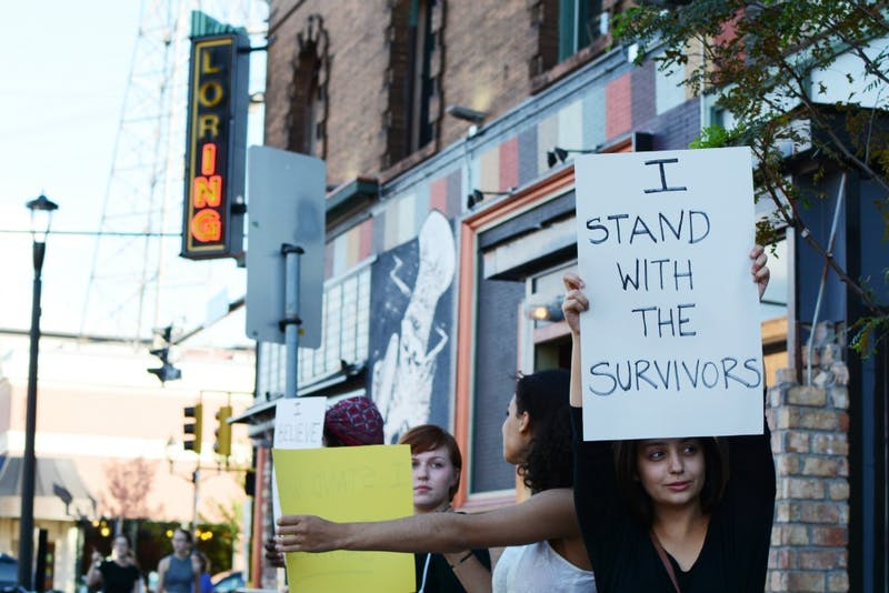 Demonstrator Bella Looney holds a sign in alliance with sexual assault survivors in front of the Loring Pasta Bar on Fourth Street on Saturday, Sept. 10, 2016 in Dinkytown. The protest was to raise awareness that Jason McLean, owner of Loring Pasta Bar and Varsity Theater, has four civil lawsuits alleging sexual abuse of minors at the Children's Theater Company during the '70s and '80s, when he worked as an actor and teaching artist.