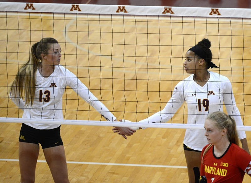 Gophers Molly Lohman, left, and Alexis Hart touch hands after a point against Maryland on Sept. 23, 2016 in the Sports Pavillon.