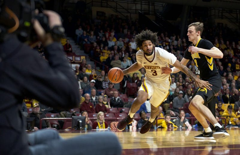The camera follows forward Jordan Murphy as he maneuvers past Iowa forward Jack Nunge during a game at Williams Arena on Wednesday, Feb. 21.