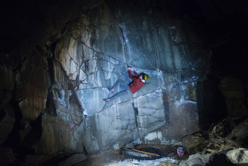 """Ethan Anderson demonstrates a winter climb of the """"Slicksides"""" boulder problem on Tuesday, Dec. 4 at Interstate State Park. Interstate is where Anderson first learned to outdoor climb three years ago."""