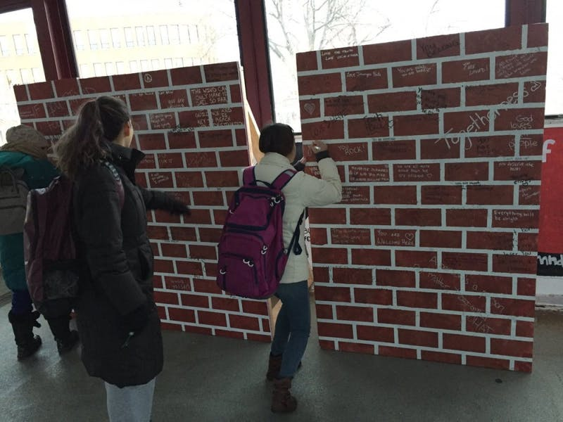 Students sign a fake brick wall that was placed in front of the College Republicans at the University of Minnesota's panels on Washington Avenue bridge on Monday, Dec. 12, 2016.