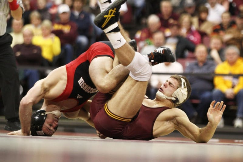 Minnesota's Dylan Ness (149) gets tangled with Wisconsin's Cole Schmidt on Sunday at the Sports Pavilion. Ness pinned No. 14 Schmidt in the first period.