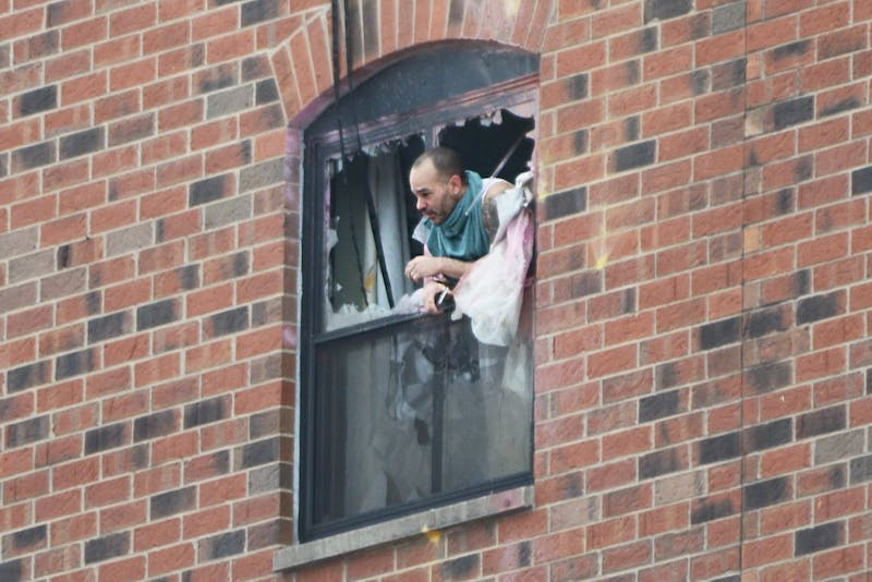 Rashad Bowman, 46, pokes his head out the sixth floor window at 11:40 a.m. after police fired gas into a room at the Graduate Hotel.