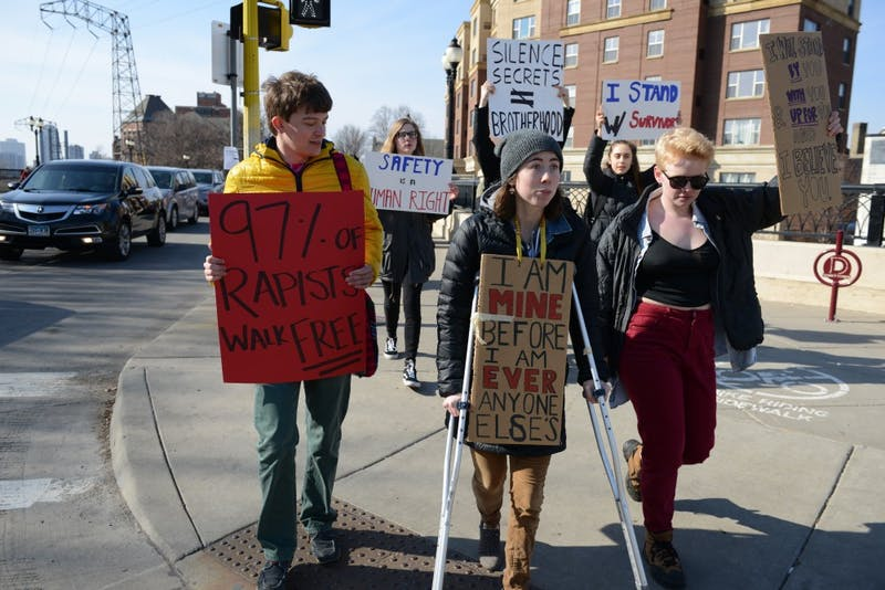 Brendan Hebert, left, and Allison Schmitz, center, march down fraternity row on University Ave. on Saturday, March 1, 2017. The event was intended to speak out against campus sexual assault.