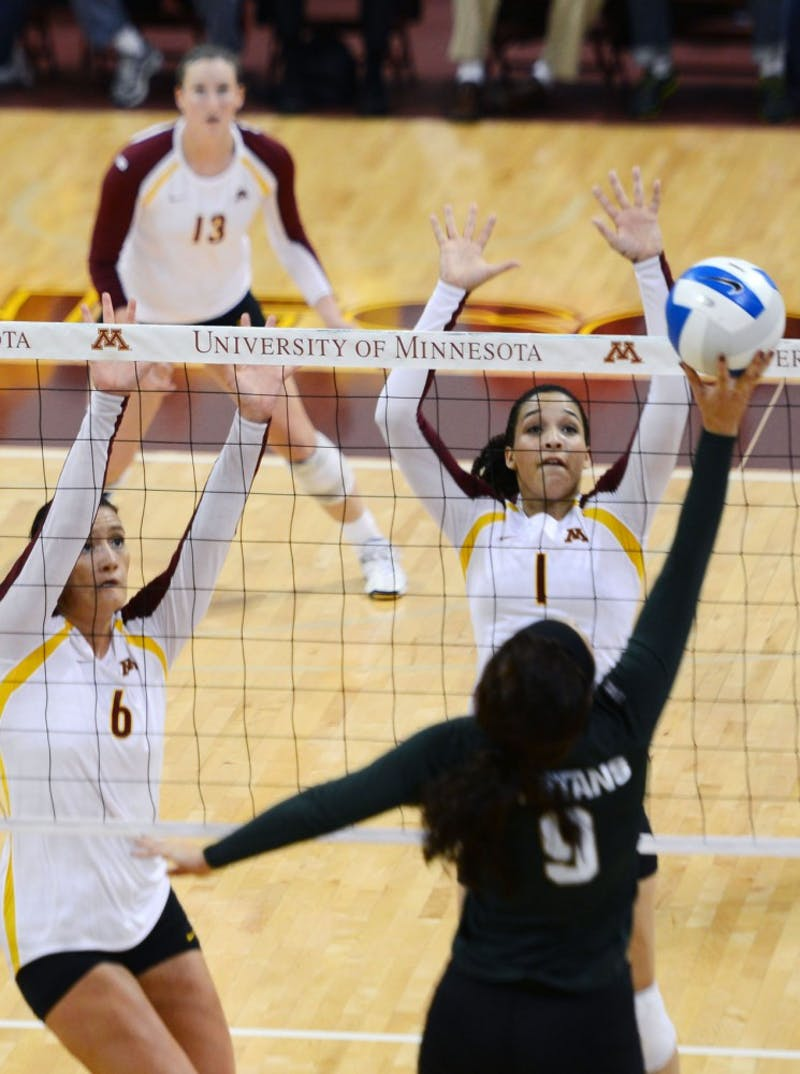 Gophers middle blocker Tori Dixon and outside hitter Daly Santana attempt to block the ball against Michigan State at the Sports Pavilion on Thursday night. Minnesota won 3-2.