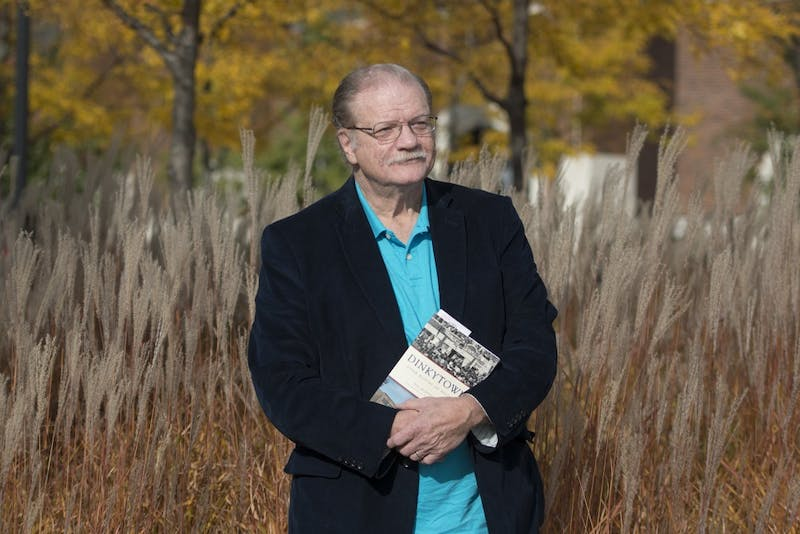 """Journalist and author Bill Huntzicker poses with his newly released book, """"Dinkytown"""" on Friday, Oct. 14, 2016 in Minneapolis."""