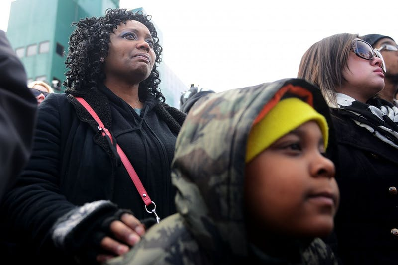"""Jennifer Oliver tears up while resting her hand on Brycen Petrie's shoulder at the beginning of the march on Monday in St. Paul. """"All of our lives matter, and you just think about your children,"""" Oliver said."""