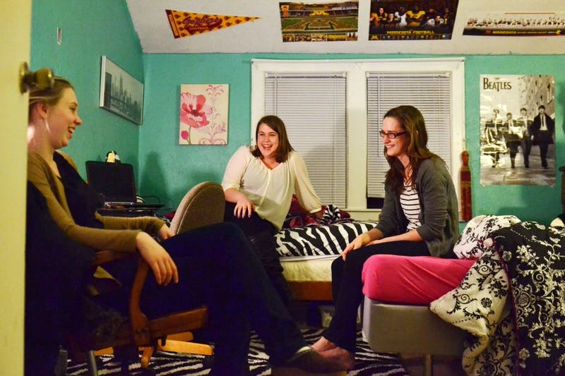 Roommates Maria Finsness, left, Maddie Hansen, center, and Emma Reese relax in one of their rooms Sunday, March 10, 2013, in their Dinkytown home. The three roommates share the home with 11 other people and said they consider rent very affordable.