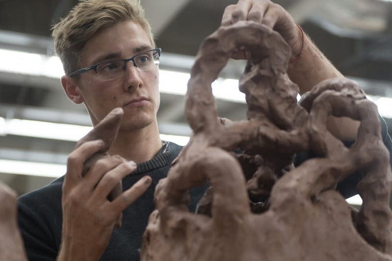 Izaak Davison-Kerwood works on his ceramic project at Regis Center For Art on Thursday.