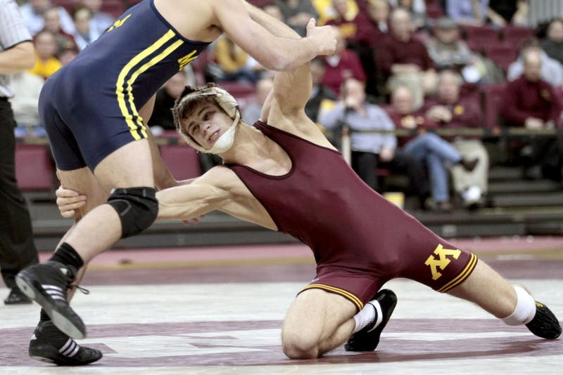 Gophers' Dylan Ness attempts to take down Michigan's Eric Grajales Jan. 27 at the Sports Pavilion.