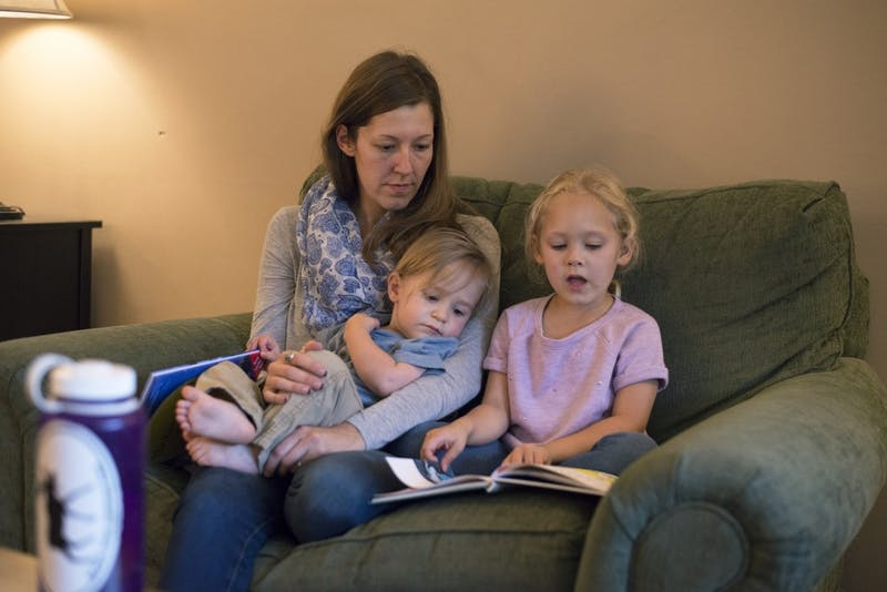 "Annabelle Stalboerger reads to her two children, 18-month-old E.J., and 5-year-old Clara on Thursday, Sept. 15, 2016 at their home in Sartell, Minnesota. Stalboerger's fiancé University of Minnesota third-year law student Edward ""Teddy"" Fleming had testified in March to help a bill pass to modify child care grant eligibility to include graduate students. They spend about $18,000 per year on child care expenses."
