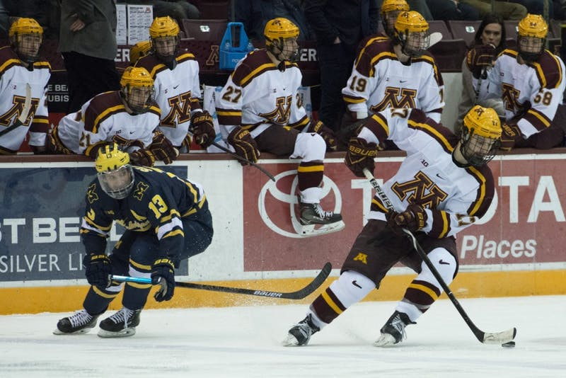 Senior forward Tommy Novak keeps the puck away from University of Michigan Junior Jake Slaker on Friday, Feb. 1 at 3M Arena at Mariucci.