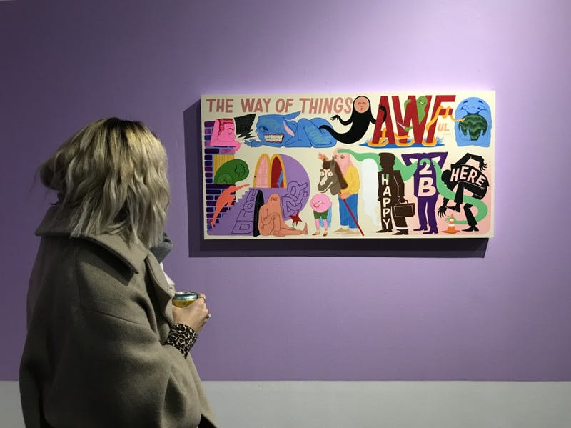 An onlooker views one of Jose Dominguez's paintings on Saturday, Nov. 17 at the Public Functionary gallery.