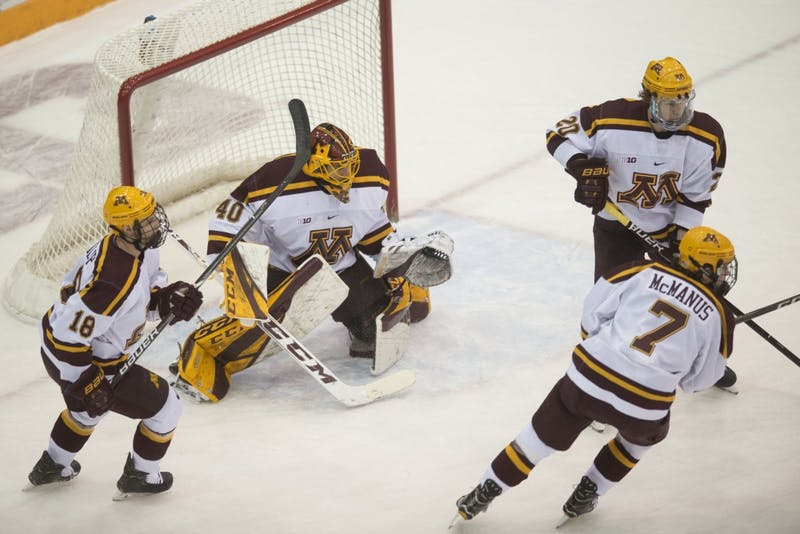 Members of the gopher men's hockey team help goalie Mat Robson keep the puck out of the net on Saturday, Jan. 26 at 3M Arena at Mariucci.