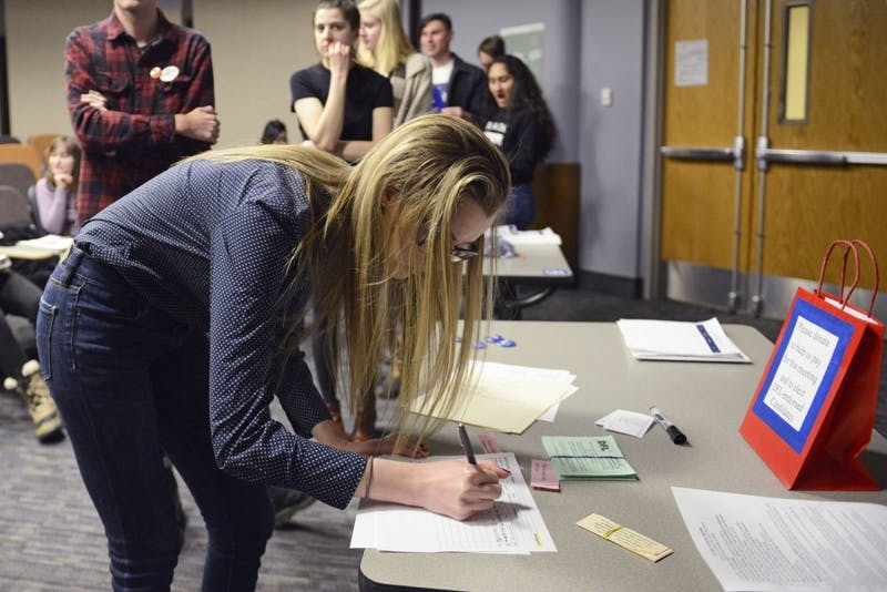 Political science freshman Katie Szarkowicz signs up to be a delegate at the state convention during the DFL Caucus on Tuesday, Feb. 6 in Murphy Hall. Szarkowicz said she attended the caucus because she thinks democracy and being engaged in one's community are important.