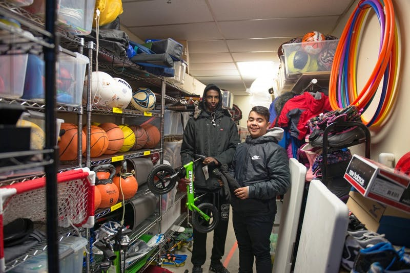 Hamsa Osman, left and Charly Tiempos founders of Sports Check it Out, a sports equipment checkout program in Cedar Riverside stand in the check out room where they rent out a variety of equipment to neighborhood kids.