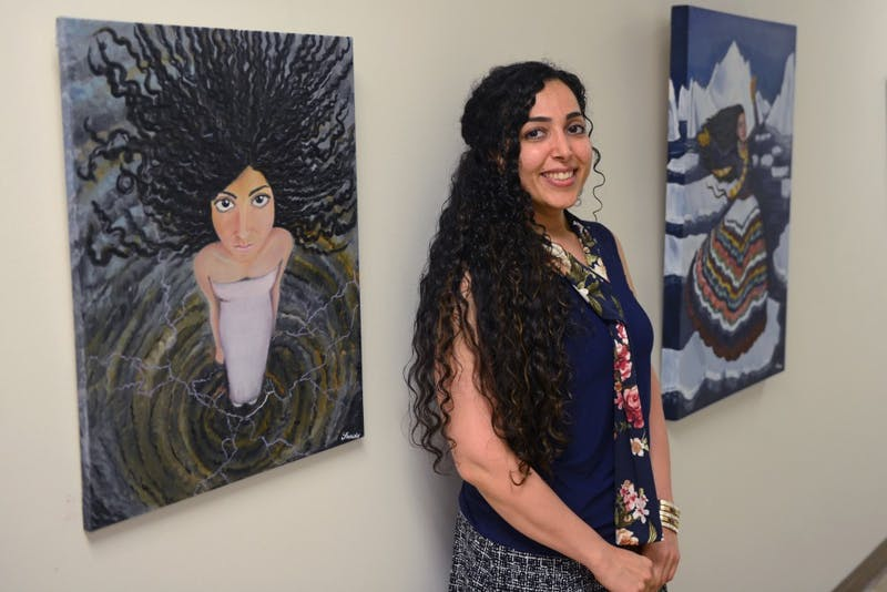Saeide Mirzaei stands beside her oil paintings exploring the experiences of immigrant women in the U.S. on the garden level of Appleby Hall on Sept. 20, 2017.