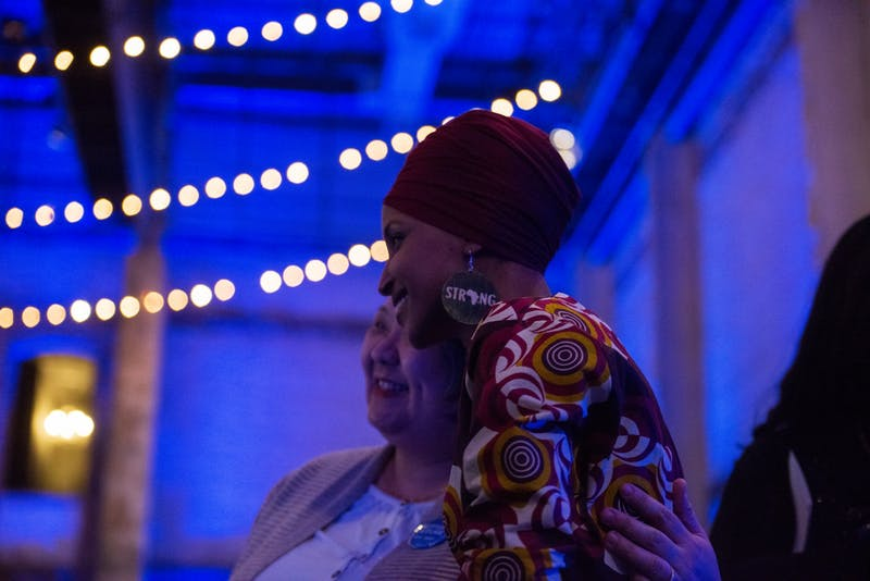 "Congresswoman Ilhan Omar hugs an attendee as their photo is being taken at Ilhan Omar 2020 Reelection Kickoff: ""Send Her Back to Congress"" at Aria on Thursday, Jan. 23. (Nur B. Adam / Minnesota Daily)"