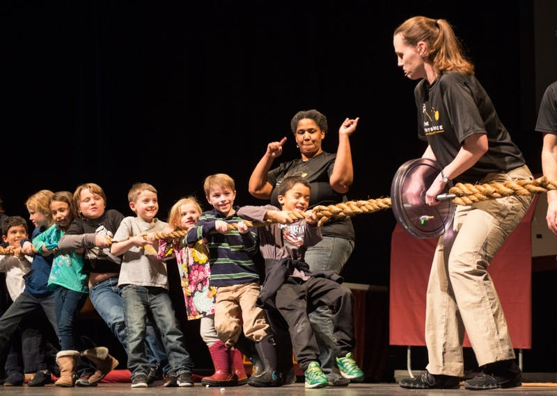 Children attempt to tug plates apart at the Physics Circus in Northrop Auditorium on Thursday. The event, hosted by the Physics Force, aimed to entertain and educate children through a variety of physical science performances.