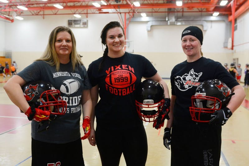 University student Nikki Graf stands in between alumnae Laura Brown (left) and Nikki Beyer at their practice in Bloomington on Saturday. Their team, the Minnesota Vixen, are the longest continuously operating women's football team in the nation.
