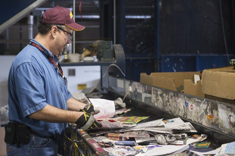 A worker at the Como recycling center sorts out recyclable paper products on a conveyor belt on Friday, July 13. The center will bring about 2,000 organics bins to every building on campus over the course of two years.