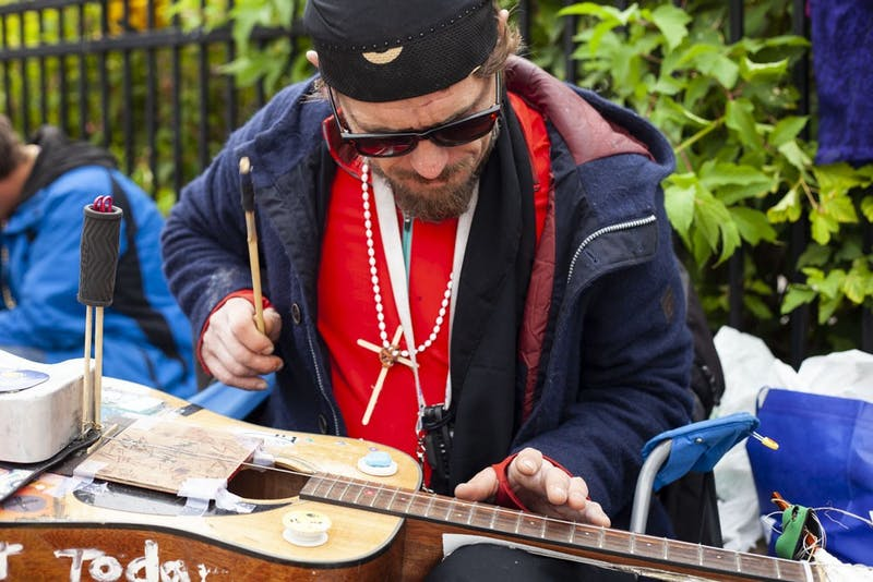 """Elijah the Prophet"" plays an original song on his custom guitar in Dinkytown on Saturday, Sept. 7. Elijah intends to use his love of music to start a program for troubled youth in the area."