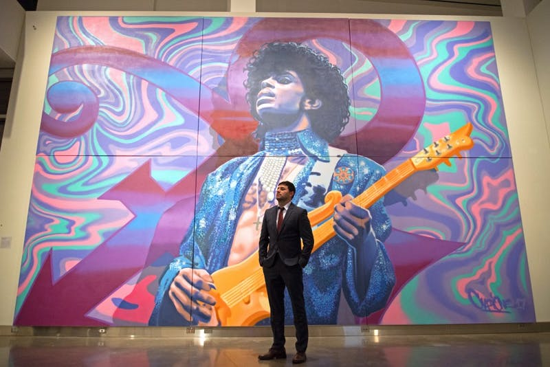 "Aerosol artist Rock Martinez poses for a portrait with the mural he created in honor of Prince inside the Weisman Art Museum during the preview party for the ""Prince from Minneapolis"" exhibition on Friday, Dec. 8. Martinez has painted large scale murals for over 15 years."
