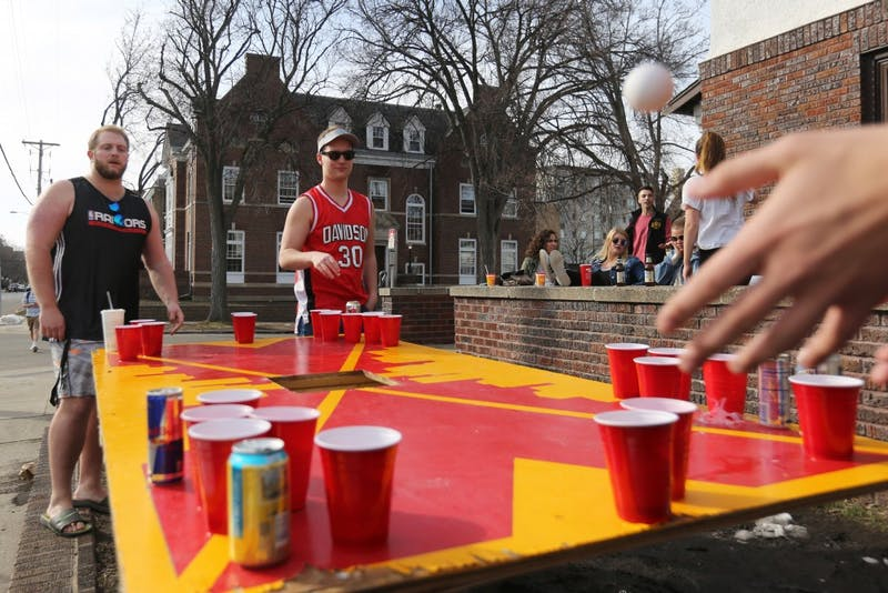 Zach Kosel and Dan Davidson watch to see if they make the cup during a beer pong game outside their fraternity on Friday, April 20 in Minneapolis.
