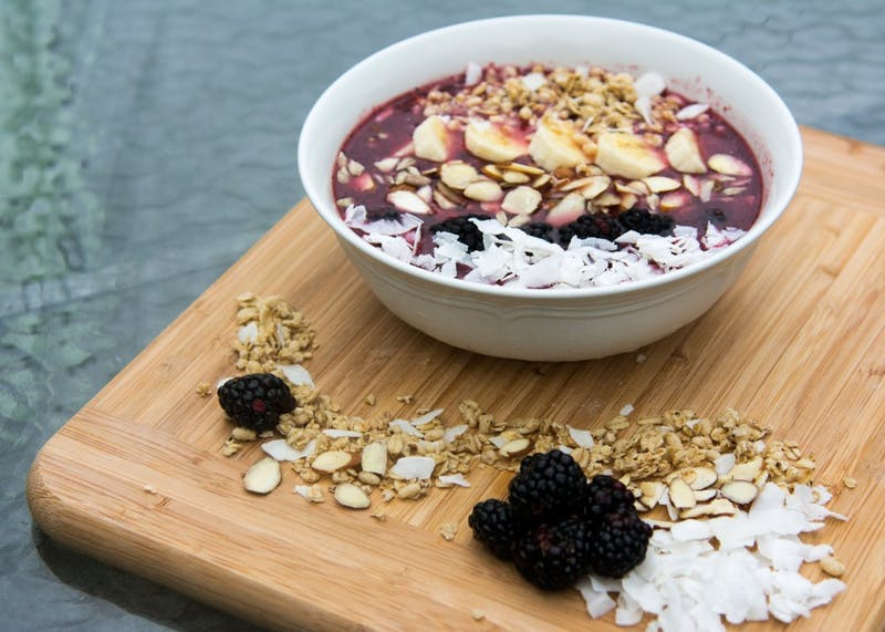 An acai bowl with shredded coconut, almonds, blackberries, banana and granola.